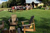 Guests mingle on a sunny mountain lawn.